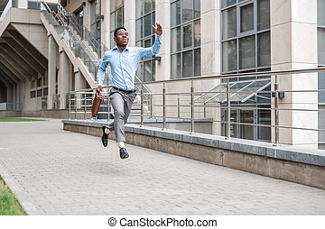businessman with briefcase running - Young African American...