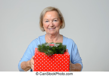 Attractive elderly lady with a large Xmas gift