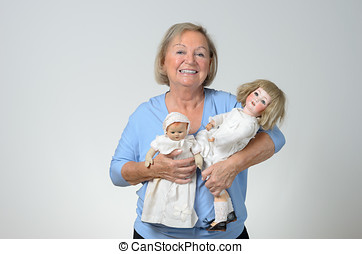 Elderly woman holding two antique dolls