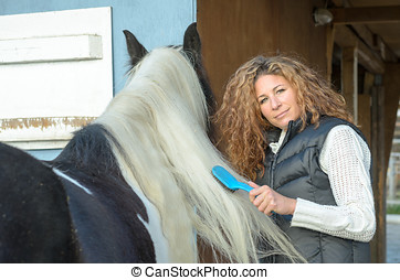 Woman combing the mane of the horse while looking at the...