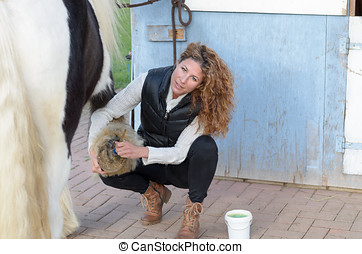 woman cleans the horse's hooves with a brush while looking...