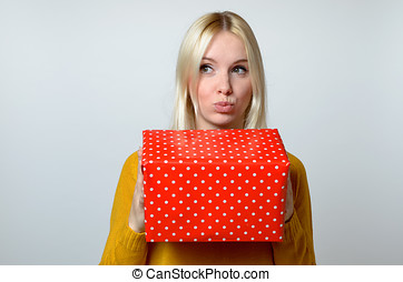 Thoughtful Woman with Pouting Lips Holding Present -...