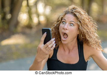 Young woman reacting in horror to a text message -...