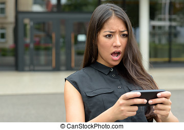 Young woman reacting in horror to an sms, text message or...