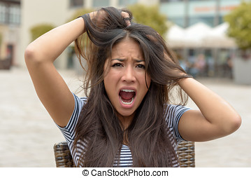 Upset frantic young woman tearing at her hair and yelling in...