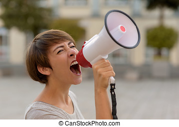 Young woman yelling into a megaphone or bullhorn