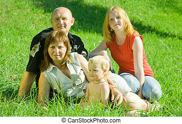 family  from four posing on grass