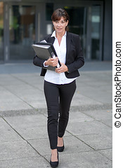 Efficient businesswoman approaching the camera