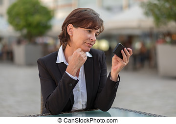 Attractive businesswoman reading a text message - Serious...
