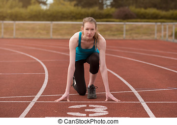 Young woman sprinter in the starter position on a race track...
