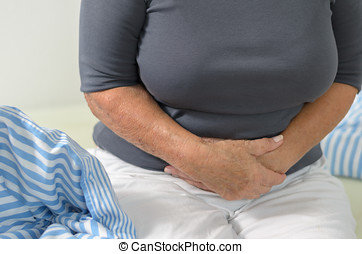 Woman with stomach ache clutching her stomach with clasped...
