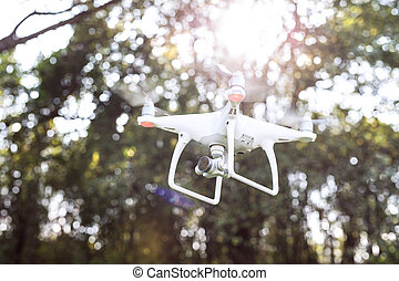 Flying helicopter drone with camera. Green sunny nature. -...