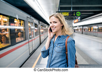 Woman making phone call at the underground platform, waiting...