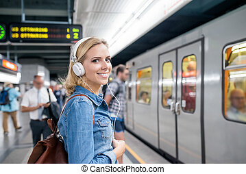 Young woman in denim shirt at the underground platform -...