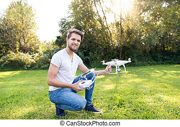 Young hipster man with drone. Sunny green nature. - Young...