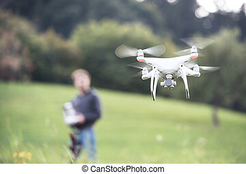 Unrecognizable man with flying drone. Sunny green nature. -...