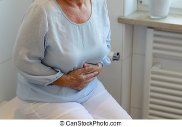 Senior woman sitting on toilet - Mid section of senior woman...