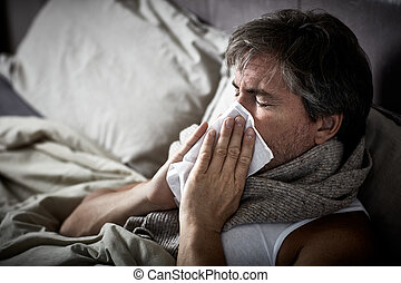 Sick man with cold lying in bed and blow nose. - Sick man...