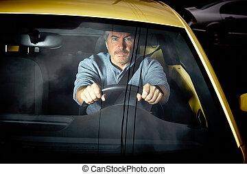 Tired man driving car at night.