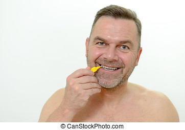 Middle aged man using interdental brush, head looking at the...