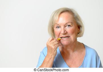 Elderly lady using interdental brush, head and shoulders...