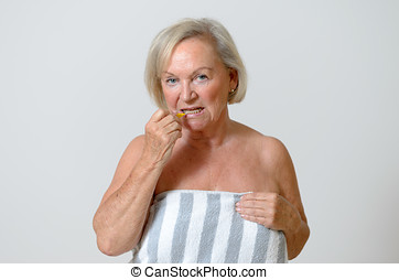 Elderly lady using interdental brush, head and shoulders...