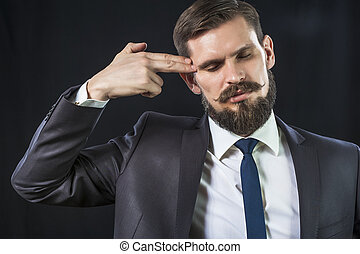 Elegant man in suit with finger's gun - Elegant businessman...