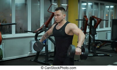 Young man does exercise with dumbbells
