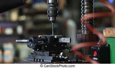 Employee drilling hole in flat steel plate - Employee...