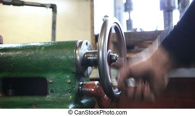 Man hand operating old controls of turning machine - Close...