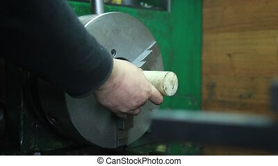 Workpiece in headstock of turning lathe machine - Man fixing...