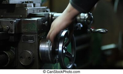 Worker controls adjustment wheel of lathe machine - Close up...