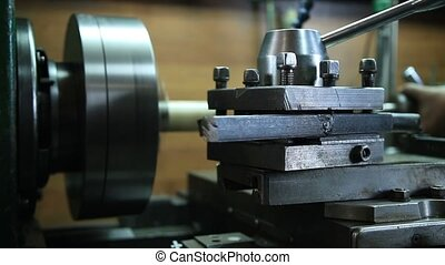 Worker in uniform operating manual lathe - Close up of tools...