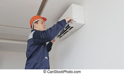 serviceman measures a air conditioning - serviceman inspects...