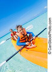 Kids paddling in kayak - Kids enjoying paddling in orange...