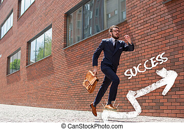 young businessman running in a city street - Young...