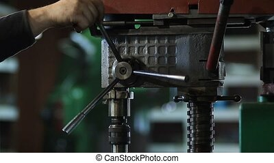 Craftsman drilling metal with drill in workshop. Worker...