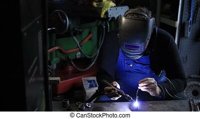 Welder man Tig welding in workshop. Manual worker welding...