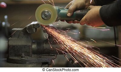Worker cutting metal workpiece with circular saw - Worker...