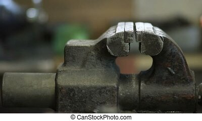Old and rusty bench vise in metalwork workshop. Worker hand...