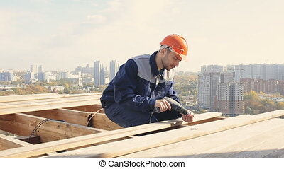 Worker on a roof with electric drill installing tile on wooden house