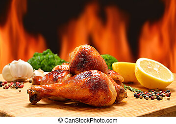 Grilled chicken legs and various vegetables on a chopping...
