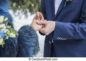 Close up groom put the wedding ring on bride, wedding in...