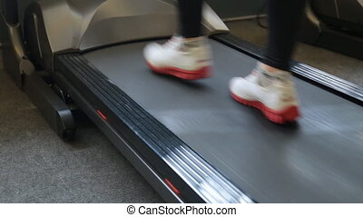 Fitness girl running on treadmill. Woman with muscular legs...