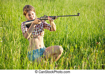aiming girl - girl aiming a pneumatic air rifle in grass...