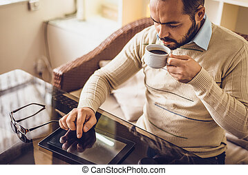 Casual Man Using Tablet Computer Sitting in Cafe Surfing Internet