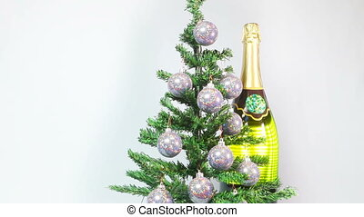 New Year's balls on a New Year tree and a huge bottle of...