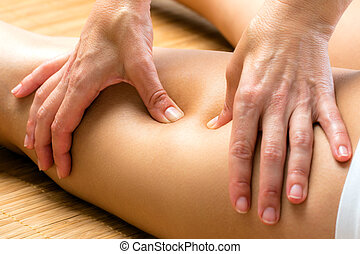 Hands applying pressure on hamstring. - Close up detail of...