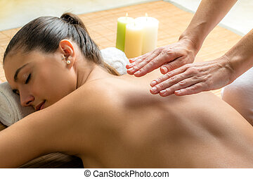 Reiki therapist doing treatment on female back.