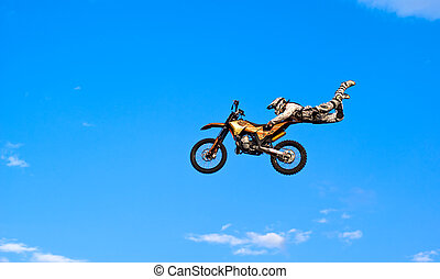 flying biker on a blue sky background